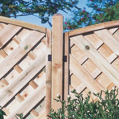 a wooden, pressure treated fence post in situ
