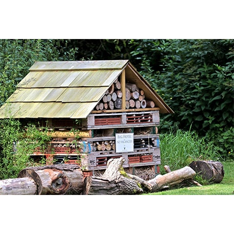 A bug hotel with a tiled apex roof, 'no vacancies' sign, surrounded by logs