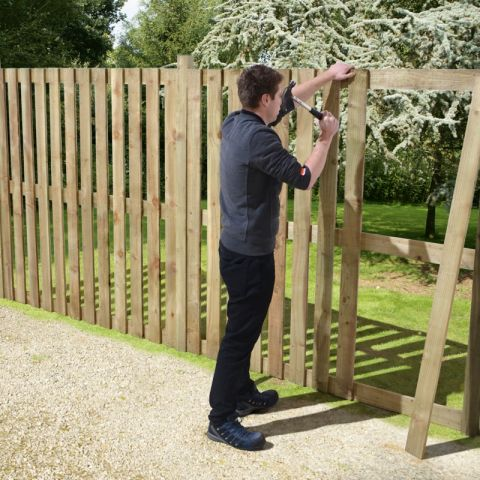 a man erecting a diy hit and miss fence panel