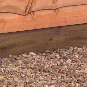 a close up of a brown gravel board protecting the bottom of a fence panel from pea gravel