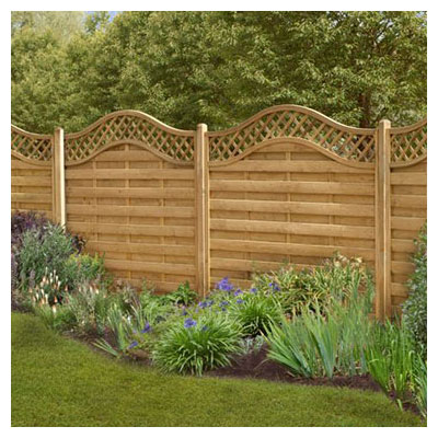 Forest 6x6 Paloma Fence Panel - Pressure treated fence panels with a wavy, diamond trellis top behind flowers and grasses