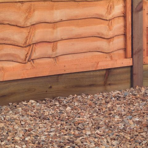 a dark brown gravel board supporting a fence panel atop some pea gravel