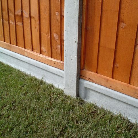 concrete gravel boards and post supporting fence panels atop some grass